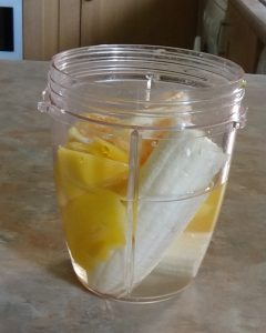 Bananas, mango, orange and water in blender jug